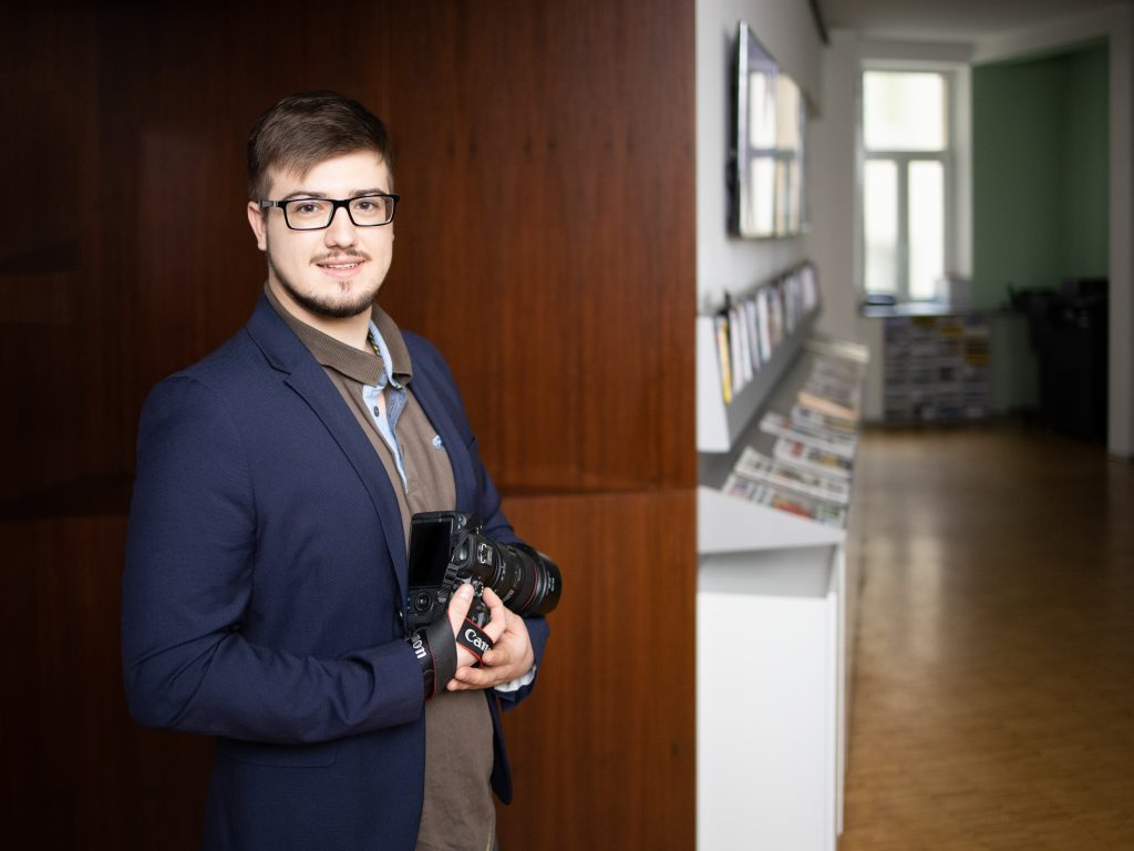 young man standing in front of wooden wall with camera in hand