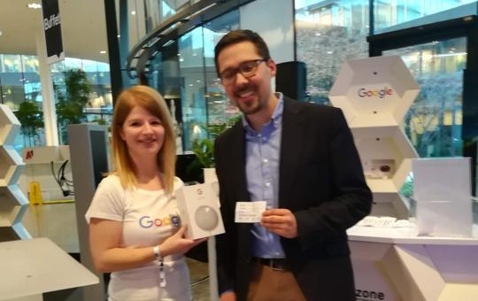 Junge blonde Frau und Mann mit Brille vor einem Messestand von Google