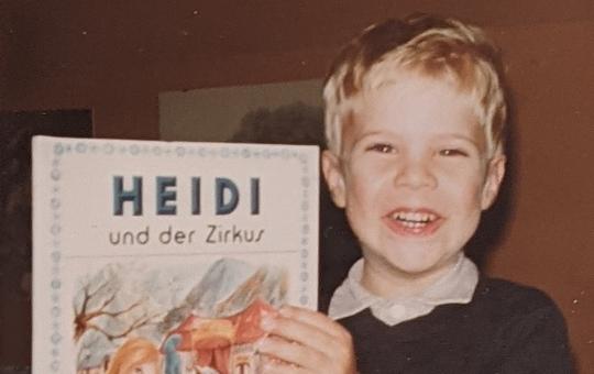 Christopher als Bub mit Bilderbuch