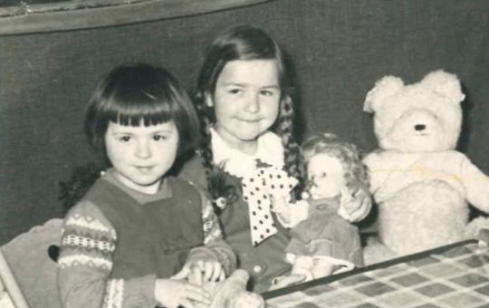 2 Mädchen mit Puppe an einem Tisch