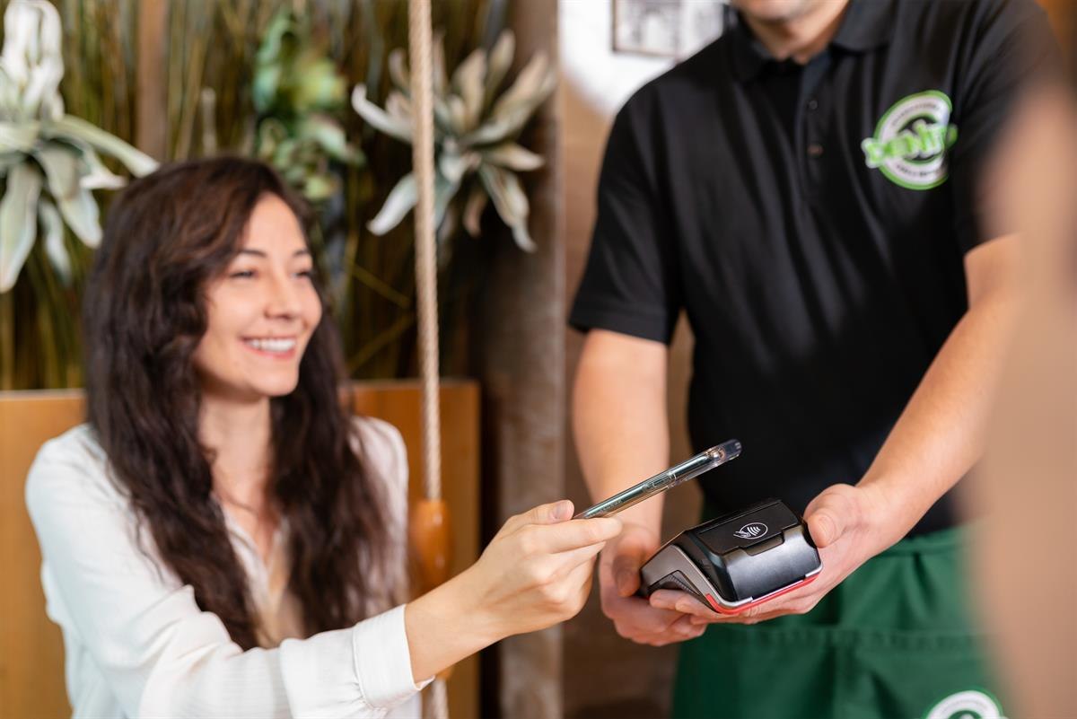 Frau bezahlt mit dem Handy am Terminal