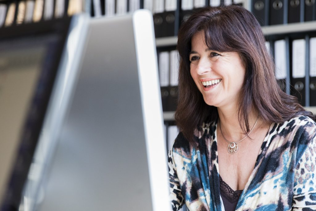 dark haired lady looking at computer screen laughing