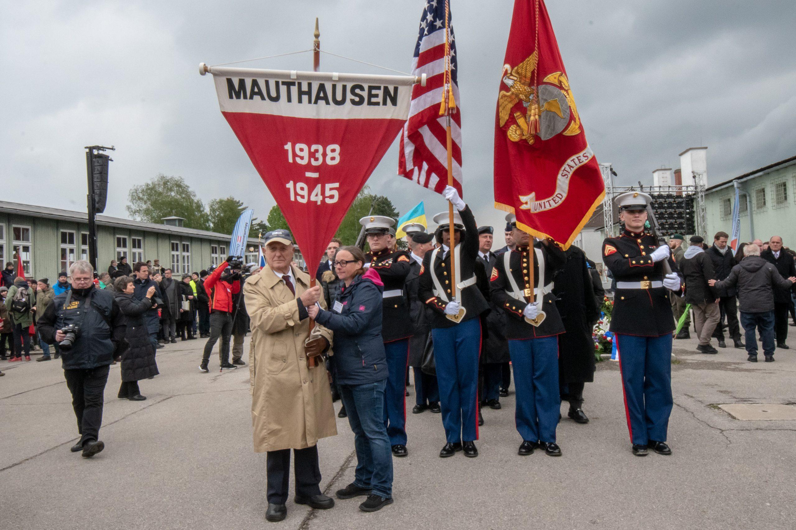 Überlebende Tragen die Fahne des KZ-Mauthausen gefolgt von US Marines und tausenden von Menschen beim Auszug aus der KZ-Gedenkstätte Mauthausen.