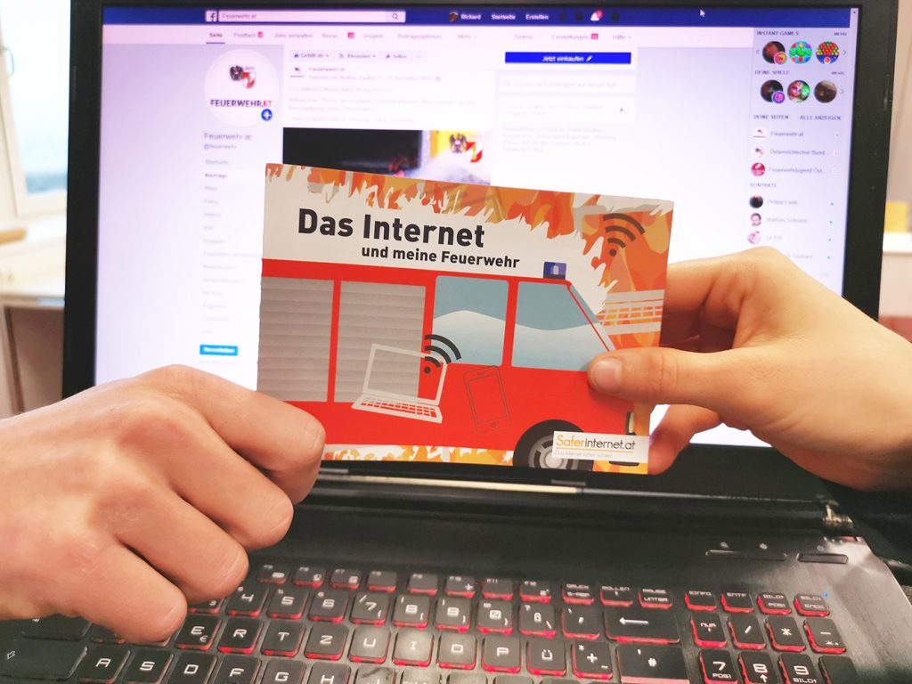 Hands holding an info brochure in front of a laptop