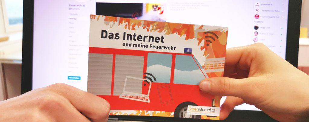 Hände halten eine Info-Broschüre vor einem Laptop