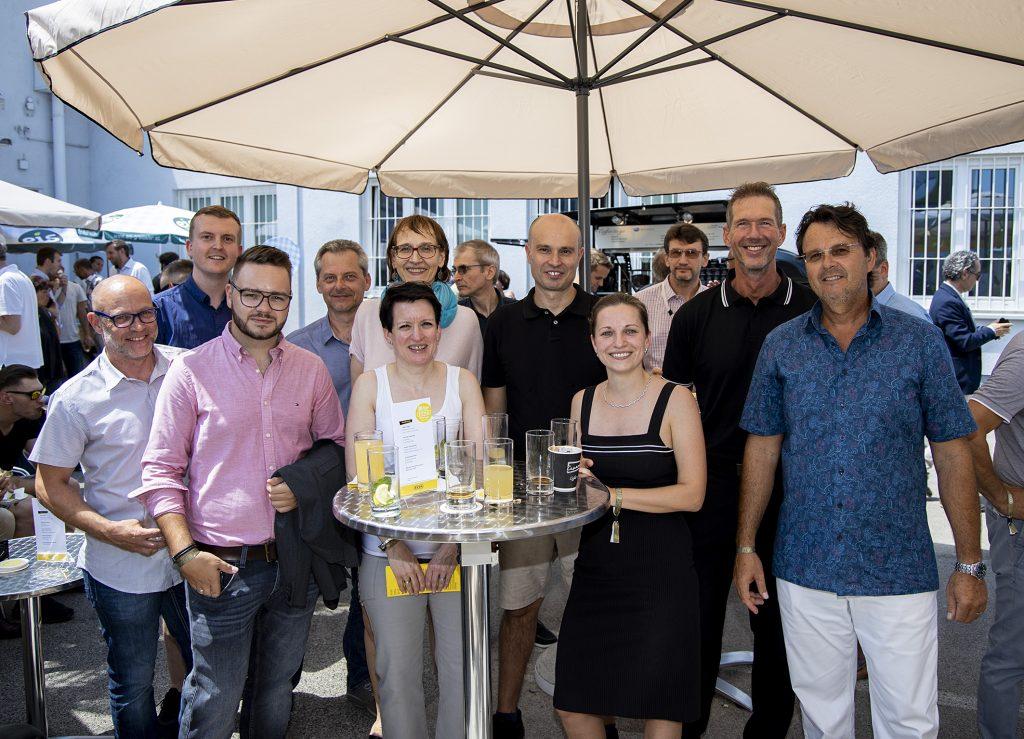 Gruppenfoto von mehreren Menschen im Sommer unter einem weißen Sonnenschirm