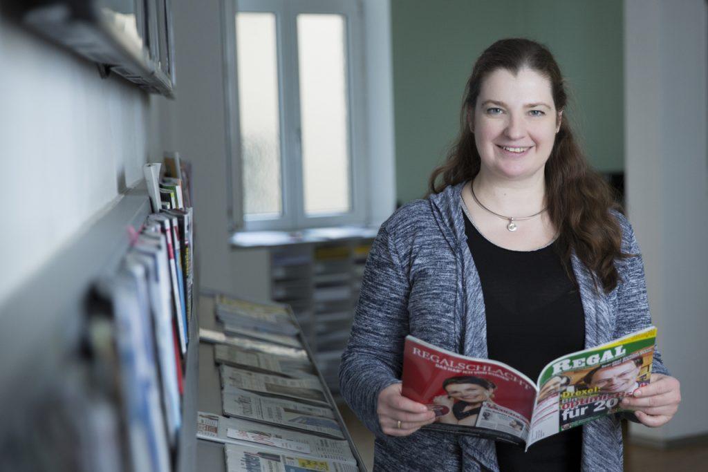 Woman with long dark hair holdung a magazine smiles