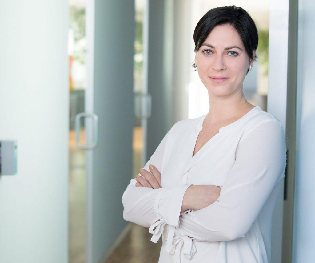 Frau mit dunklen Haaren und weißer Bluse