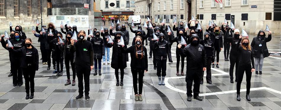 Schwarz gekleidete Personen mit Haiflossen in der Handn
